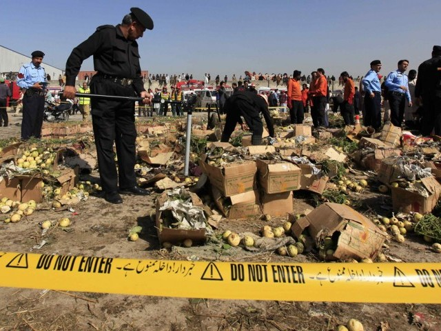 A police official uses a metal detector to search the site of a bomb blast at a vegetable and fruit market in the outskirts of Islamabad April 9, 2014. PHOTO: REUTERS