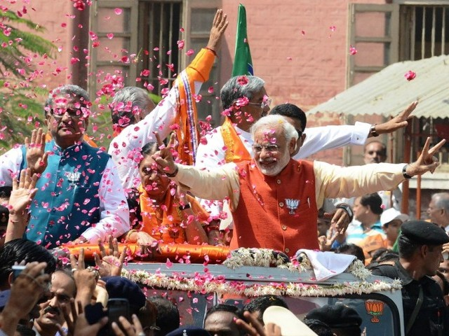 In this photograph taken on April 9, 2014, Chief Minister of the western Indian state of Gujarat and Bhartiya Janta Party (BJP) prime ministerial candidate, Narendra Modi (C) is showered with flower petals during his roadshow in Vadodara, some 110 kms from Ahmedabad, prior to filing his nomination papers for the forthcoming elections. PHOTO: AFP