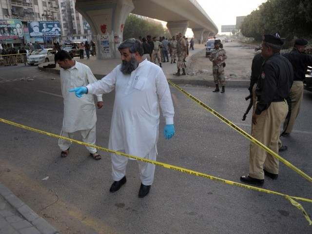 Investigators work at the scene after the attack on prominent Pakistani journalist Hamid Mir in Karachi on April 19, 2014. PHOTO: AFP