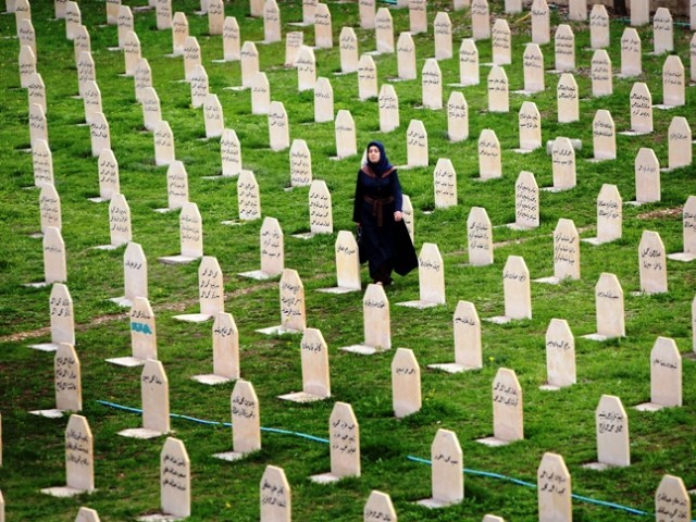 A file picture taken on March 16, 2014 shows an Iraqi Kurd woman visiting a grave yard for the victims of a gas attack by former Iraqi president Saddam Hussein in 1988, as people mark the 26th anniversary of the attack in the Kurdish town of Halabja, 300 kms northeast of Baghdad. PHOTO: AFP