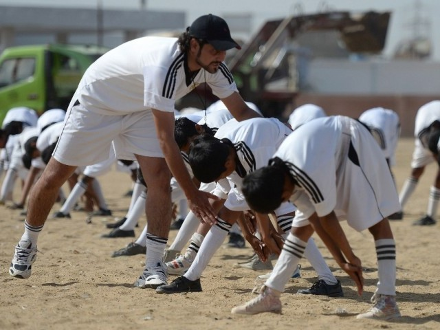 Academy coach Mohsin Shah (L) instructs local youth as they participate in a training session at a local stadium in Karachi. PHOTO: AFP