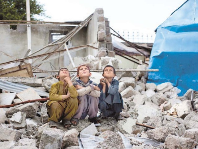 Afghan children sitting on the remains of the Pehli Kiran school. PHOTO: FILE/EXPRESS