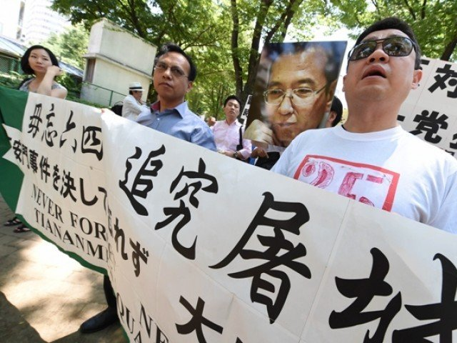 Former Chinese dissident leader Wu'er Kaixi (R) and activists hold a banner and a poster of jailed Nobel Peace Prize laureate Liu Xiaobo, as they march during a rally in Tokyo on June 1, 2014, ahead of the 25th anniversary marking the brutal crushing of the Tiananmen Square protests. PHOTO: AFP