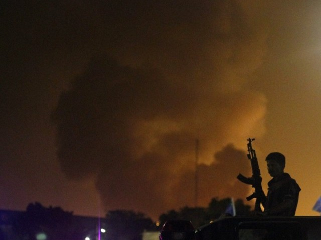 A policeman with a gun stands on a vehicle as smoke bellows from Jinnah International airport in Karachi June 9, 2014. PHOTO: REUTERS