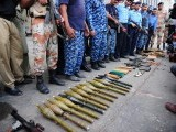 Pakistani policemen show seized weapons after militants attacked Jinnah International Airport in Karachi on June 9, 2014. PHOTO: AFP