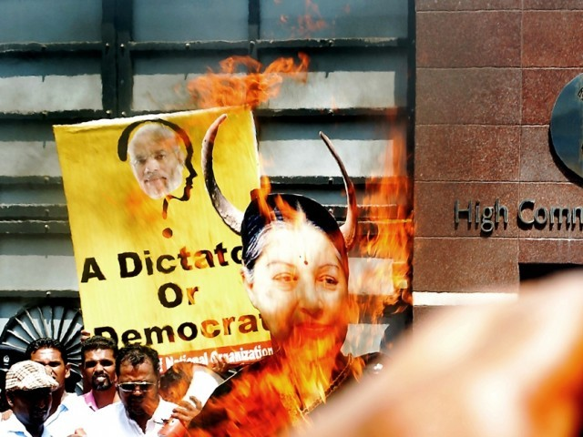 Sri Lankan pro-government supporters burn a larger-than-life photograph of Tamil Nadu state Chief Minister Jayalalitha Jayaram during a demonstration outside the Indian High Commission in Colombo on June 10, 2014. The activists denounced India s new Prime Minister Narendra Modi and Jayaram for allegedly interfering in Sri Lanka s domestic politics. PHOTO: AFP