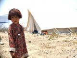 An internally displaced girl, fleeing a military operation in the North Waziristan tribal agency, looks on at a makeshift refugee camp in Bannu on June 28, 2014.