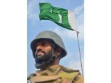 Soldier standing under Pakistani flag after clearance of Mirali Bazar. PHOTO: ISPR