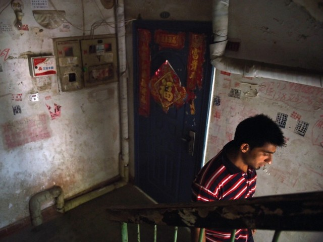 This photo taken on June 18, 2014 shows a Pakistani refugee as he walks past Chinese decorations in the stairwell of his apartment building in Sanhe, in China's Hebei province, east of Beijing. PHOTO: AFP