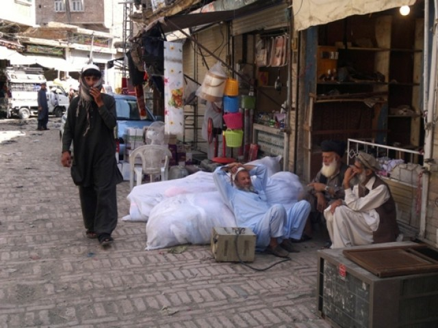 In this photograph taken on June 13, a shopkeeper leans against his belongings as he waits to leave Miramshah. PHOTO: AFP