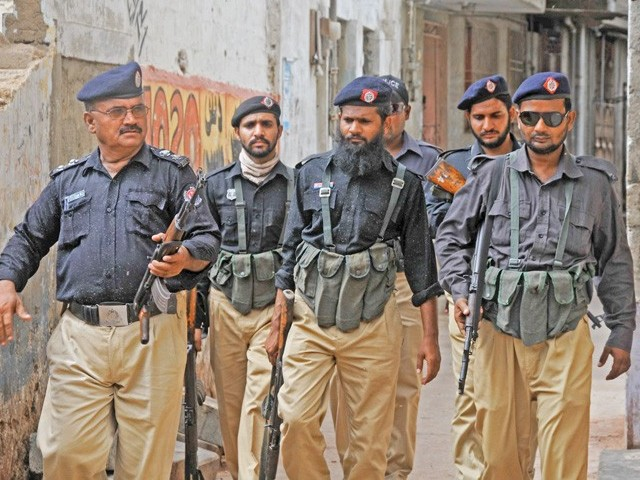 Policemen patrol the street during a targeted raid in Chanesar Goth. Karachi police and Rangers personnel have jointly conducted several hundred raids in the city. PHOTO: FILE