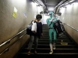 "Tadahiro Kanemasu aka the ""Carry-Your-Pram-Ranger"" carries a woman's shopping cart at the station in Tokyo August 23, 2013. In a green outfit with silver trim and matching mask, a superhero waits by the stairs of a Tokyo subway station, lending his strength to the elderly, passengers lugging heavy packages and mothers with baby strollers. PHOTO: REUTERS"