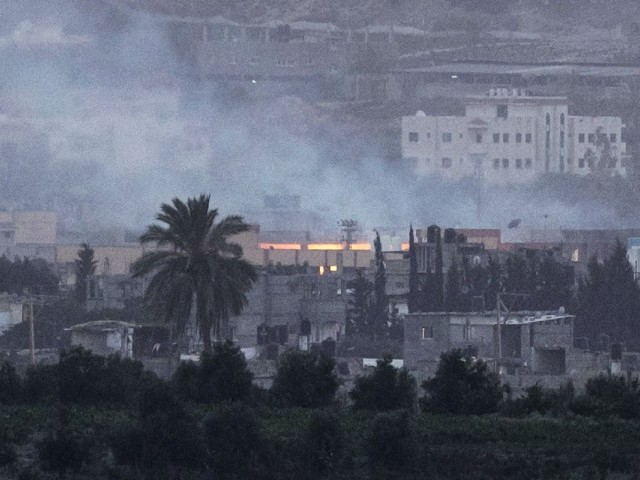 A picture taken from the southern Israeli Gaza border shows smoke billowing from a building in the coastal Palestinian enclave following an Israeli air strike on July 24, 2014. PHOTO: AFP