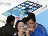 a-staff-of-a-china-mobile-shop-r-explains-a-function-of-the-iphone-5s-to-a-customer-in-beijing