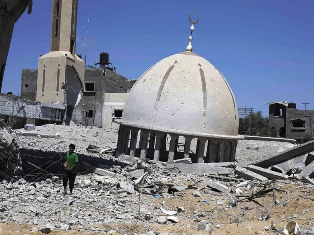 A Palestinian boy stands next to the remains of a mosque in Khuzaa town, which witnesses said was heavily hit by Israeli shelling and air strikes during Israeli offensive, in the east of Khan Younis in the southern Gaza Strip August 6, 2014. PHOTO: AFP