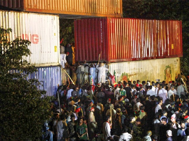 Pakistan Awami Tehreek remove containers and barricades as they march towards the Red Zone. PHOTO: REUTERS/AFP