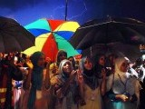PTI supporters holding umbrellas to avoid rain during sit-in protest in fron of Parliament House on Friday. PHOTO: ONLINE