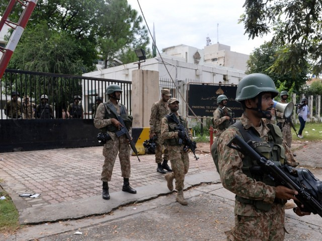Soldiers stand guard outside the headquarters of state-owned Pakistani Television (PTV) after the building was stormed by supporters of Tahirul Qadri and Imran Khan during anti-government protests in Islamabad on September 1, 2014. PHOTO: AFP