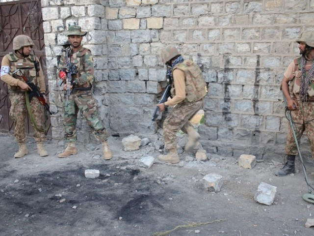 In this file photo, army men take position to clear an area in North Waziristan. PHOTO: ISPR