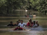 Flood victims wade through a flooded area along a road as they wait for help, in Multan, September 13, 2014. PHOTO: REUTERS