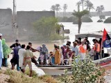 Police officials move people from flood-hit areas around Shershah Bund to safety. PHOTO: ONLINE