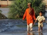 Residents wade through floodwater in the Muzaffargarh district of Punjab province on September 17, 2014. PHOTO: AFP