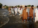 Flood victims wade through a flooded area in Muzaffargarh, Punjab province September 17, 2014.PHOTO: REUTERS
