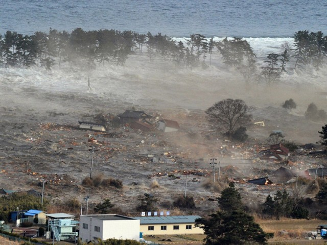 Houses are swept by a tsunami in Natori City, March 11, 2011, after a massive 8.9 magnitude quake hit northeast Japan. PHOTO: REUTERS