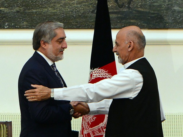 Afghan presidential candidates Abdullah Abdullah (L) and Ashraf Ghani Ahmadzai shake hands after signing a power-sharing agreement at the Presidential Palace in Kabul on September 21, 2014. PHOTO: AFP
