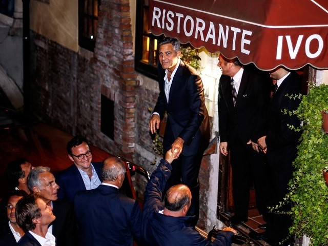 George Clooney (top L) prepares to get in a boat as he leaves the restaurant Da Ivo with friends and his father during his stag night event in Venice on September 27, 2014. Clooney and his Lebanon-born British fiancee Amal Alamuddin arrived in Venice on September 26 for a spectacular waterfront wedding billed as the party of the year. PHOTO: AFP