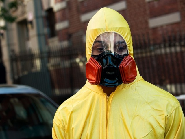 A young man, dressed in a biohazard costume, stands on the corner of 546 West 147th Street on October 25, 2014 in New York City. PHOTO: AFP