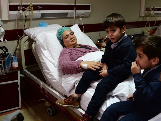 In this photograph taken on November 21, 2014, Afghan member of Parliament Shukria Barakzai interacts with her children Turan (C) and Usman (R) as she recuperates at a government hospital in Kabul following an assassination attempt. PHOTO: AFP