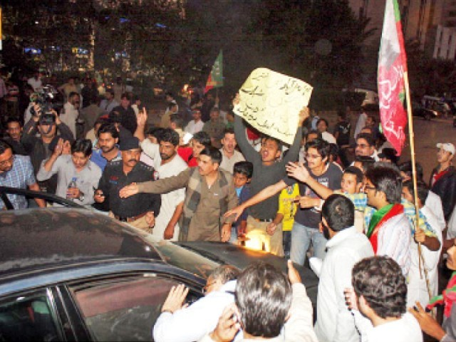 PTI supporters obstruct the path of a car on Sharae Faisal in Karachi, after coming out on the streets to protest the incidents of violence in Faisalabad. PHOTO: ONLINE