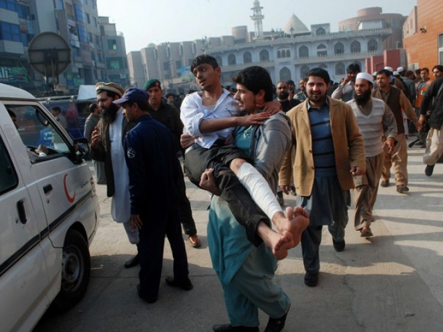 A man carries a student, who was injured during an attack by Taliban gunmen on the Army Public School, after he received treatment at a hospital in Peshawar. PHOTO: REUTERS