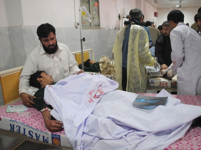 A man comforts his son, who was injured during an attack by Taliban gunmen on the Army Public School, at Lady Reading Hospital in Peshawar, December 16, 2014. PHOTO: REUTERS