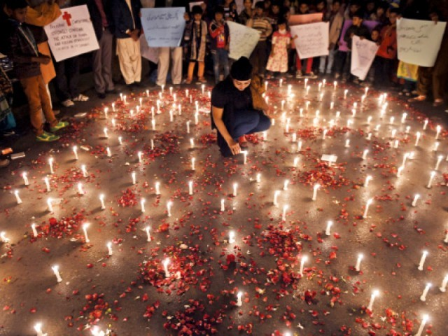 A girl lights candles for the Peshawar victims. PHOTO: AFP