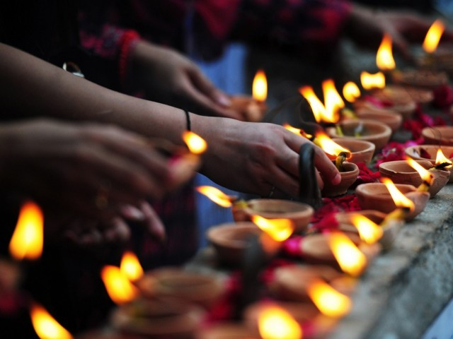 Human rights activists light lamps as they take part in a demonstration in Karachi on December 18, 2014 to express solidarity with the unfortunate victims of December 17, 2014 tragedy. PHOTO: AFP