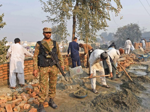 Labourers at work amid tight security at Army Public School. PHOTO: AFP