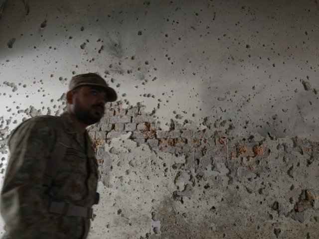 An army soldier walks past a bullet-riddled wall at the Army Public School in Peshawar on December 17, 2014. PHOTO: AFP