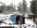 Men stand outside a roadside shop in the snow-decked hills of Murree as the region witnessed the season's first snowfalll on January 14, 2015. PHOTO: ONLINE