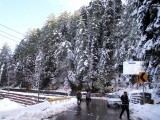 A man takes a picture on the snow covered road to Murree. PHOTO: ONLINE