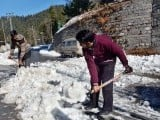 Locals shovel snow from the Nathiagali road after the first snowfall of the year. PHOTO: APP