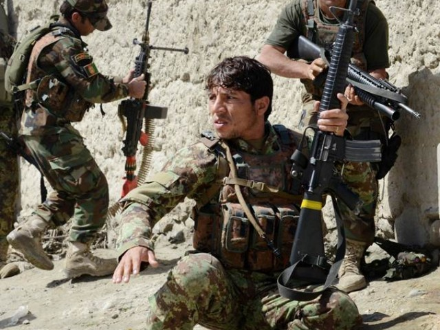 In this photograph taken on March 19, 2014, Afghan soldiers from the 4th Brigade, 201 Army Corps of the Afghan National Army (ANA) take positions behind an adobe wall after being fired upon by insurgents during an operation in Khogyani District. PHOTO: AFP