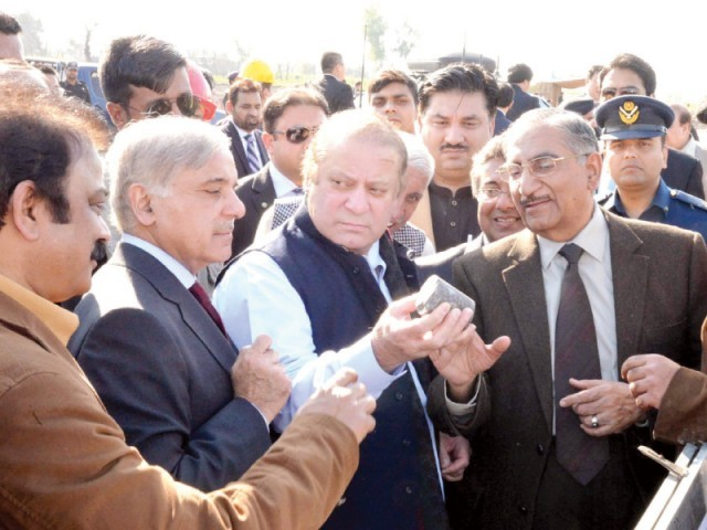 Prime Minister Nawaz Sharif and Punjab CM Shahbaz Sharif inspect a piece of iron ore at the site of excavation in Chiniot. PHOTO: PPI