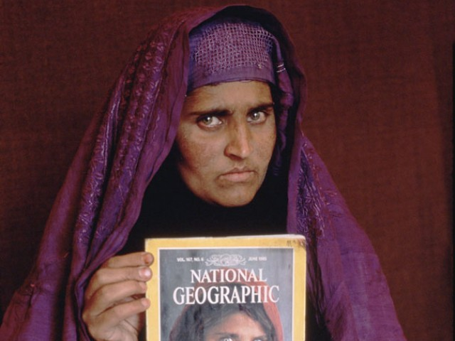 An image of Sharbat Bibi holding the cover she was featured in June 1985. PHOTO: STEVE MCCURRY