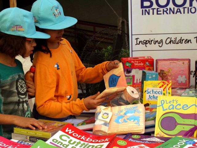 Two children look at books during the Children's Literature Festival. PHOTO: INP