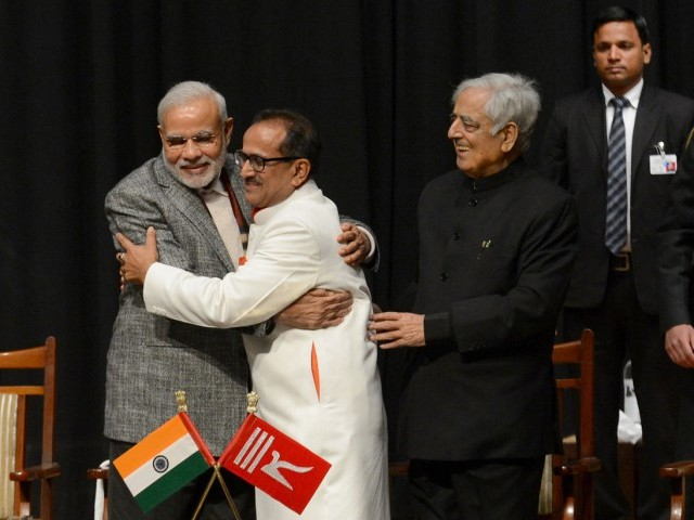 Indian Prime Minister Narinder Modi (L) and Jammu and Kashmir Deputy Chief Minister Nirmal Singh (C) embrace as Jammu and Kashmir Chief Minister Mufty Mohammed Sayeed (R) looks on during a swearing in ceremony of the state assembly in Jammu on March 1, 2015. PHOTO: AFP