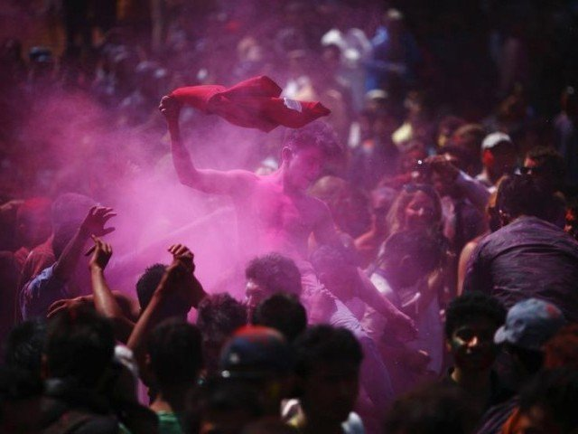 People throw colored powder as they celebrate holi, the Festival of Colors, in Kathmandu March 26, 2013. PHOTO: REUTERS