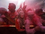 Hindu devotees stand amid a cloud of red colored powder during Holi celebrations at the Bankey Bihari temple in Vrindavan in the northern Indian state of Uttar Pradesh. PHOTO: REUTERS