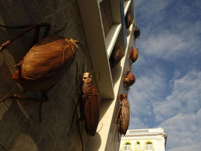 Sculptures of cockroaches with human faces appear to climb up the facade of the Museo de Bellas Artes during an exhibition in Havana. PHOTO: REUTERS